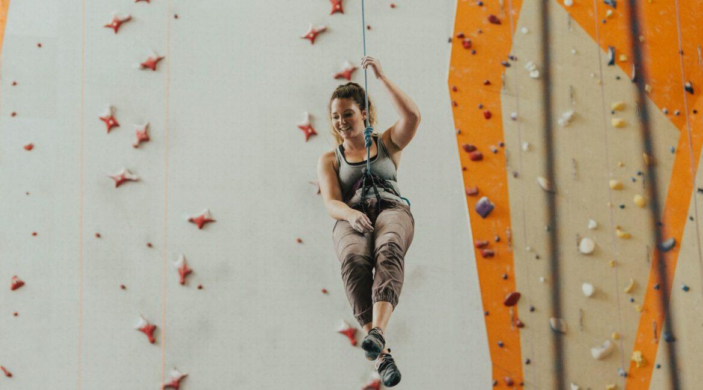Frau beim Klettern in einer Boulderhalle