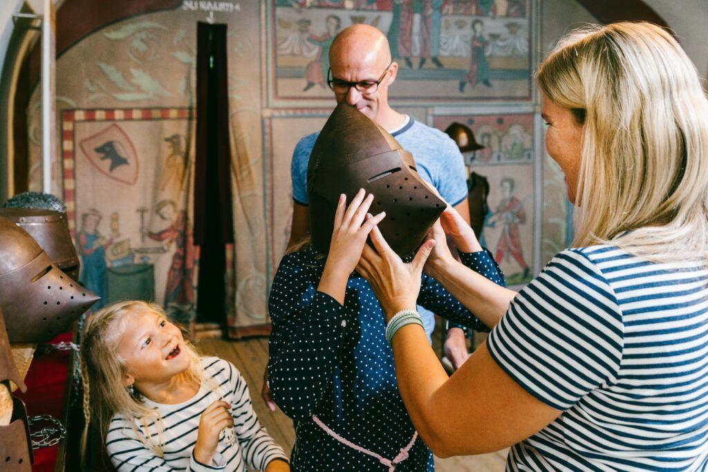 Familie beim Anziehen eines Ritterhelmes in den Burgwelten Ehrenberg